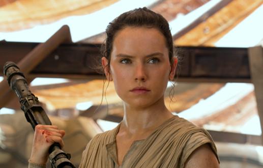Rey holding her quarterstaff on Jakku in The Force Awakens