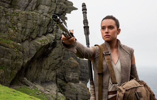 Rey offering a lightsaber to Luke on Ahch-To